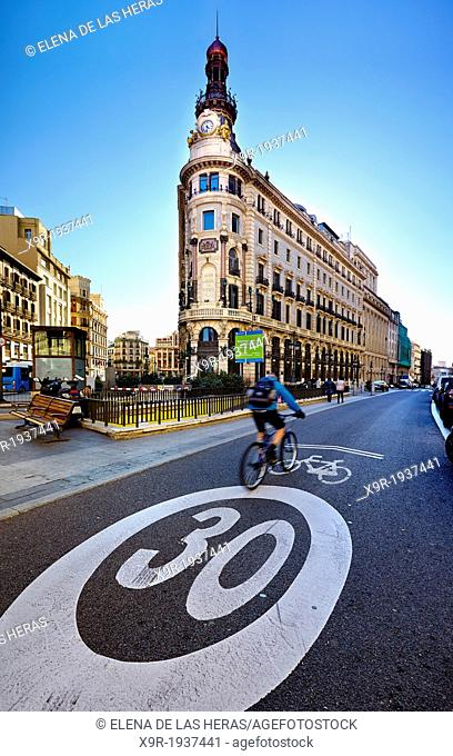Cyclist passing by the 'Banco Español de Credito' building in Alcalá street. Madrid. Spain