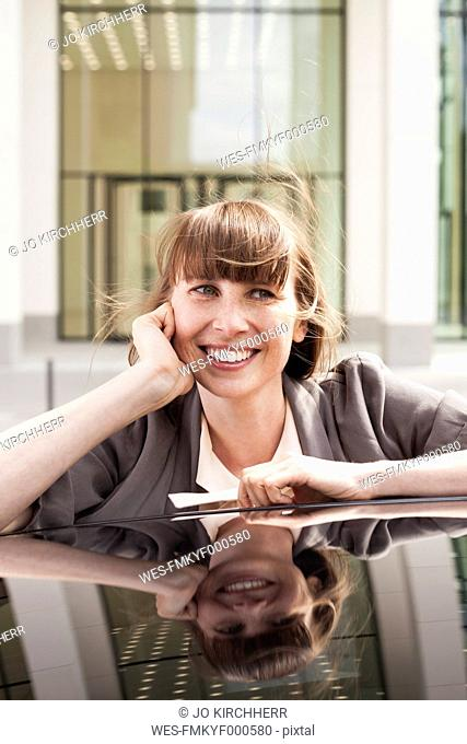 Germany, Hesse, Frankfurt, portrait of smiling businesswoman leaning on car roof