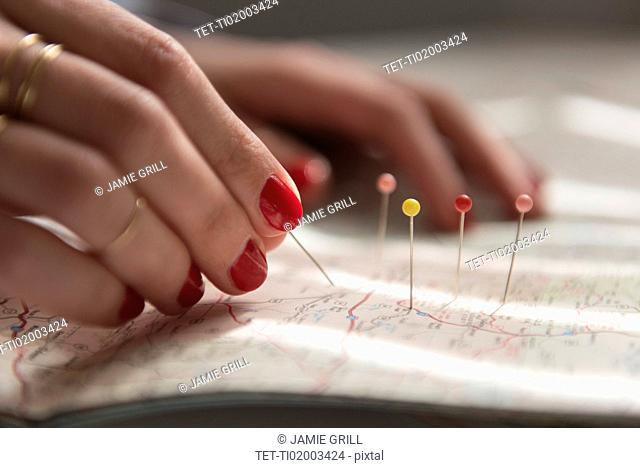 Woman applying pins on map
