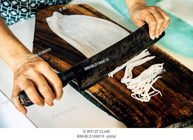 Close up of chef chopping squid on cutting board