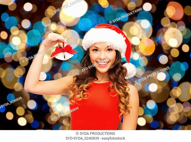 happy woman in santa hat with christmas bells