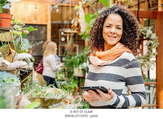 Mixed race employee using digital tablet in plant nursery