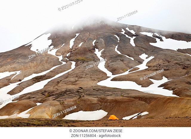 Ein Zelt an einem teilweise mit Schnee bedecktem Rhyolith-Berg, Hochtemperaturgebiet Hveradalir, Kerlingarfjoell, Island, Europa