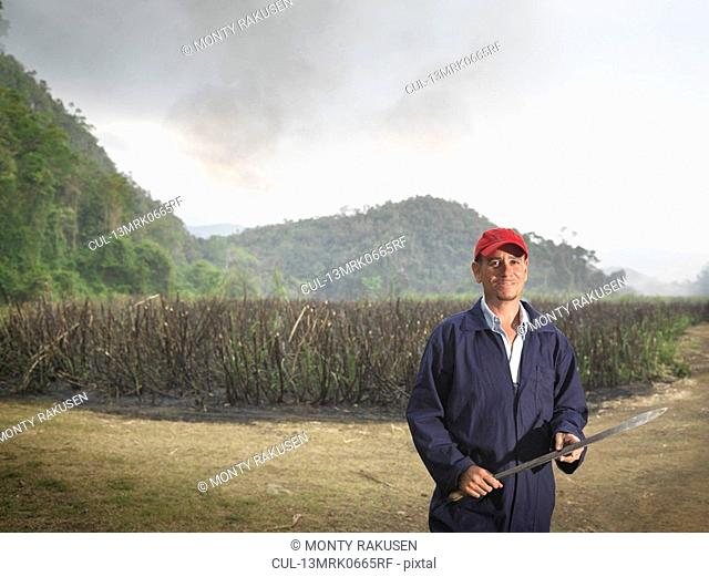 Worker With Machete And Burnt Sugar Cane