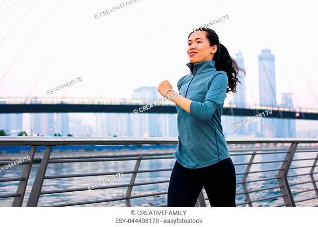Girl running in a modern city environment, urban runner