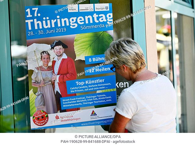 28 June 2019, Thuringia, Sömmerda: A woman hangs a poster for Thuringia Day on a shop floor. The Thuringia Day takes place from 28.06.2019 to 30.06