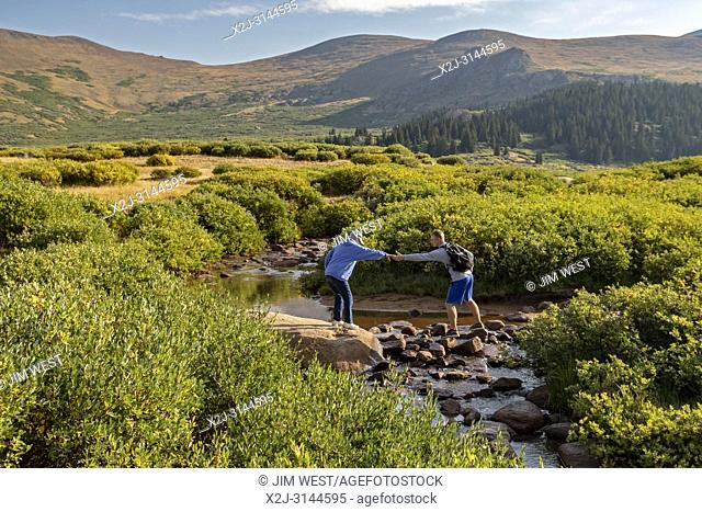 Georgetown, Colorado - An older woman gets help from a younger man in crossing a stream on the trail from Guanella Pass to 14,060-foot Mt