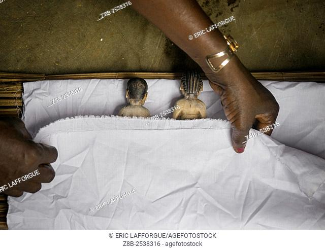 Benin, West Africa, Bopa, miss hounyoga putting the carved wooden figures made to house the soul of her dead twins in a bed