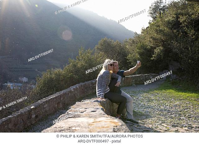 Couple sits on stone wall and takes selfie