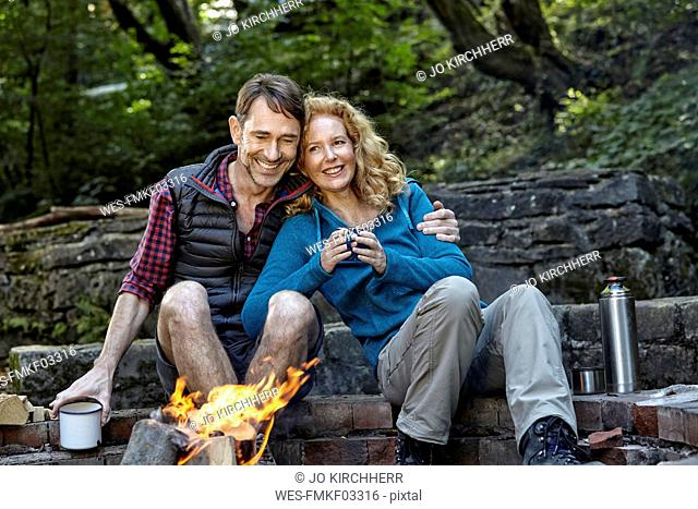 Happy couple sitting at camp fire