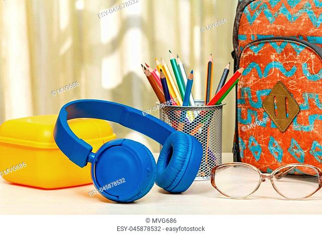 School backpack with school supplies. Metal stand for pencils with color pencils, yellow sandwich box, headphones and glasses on wooden table