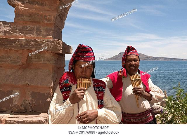 Peru, Lake Titicaca. Taquile Island indian man playing Andean reed flute or zampo–a panpipe