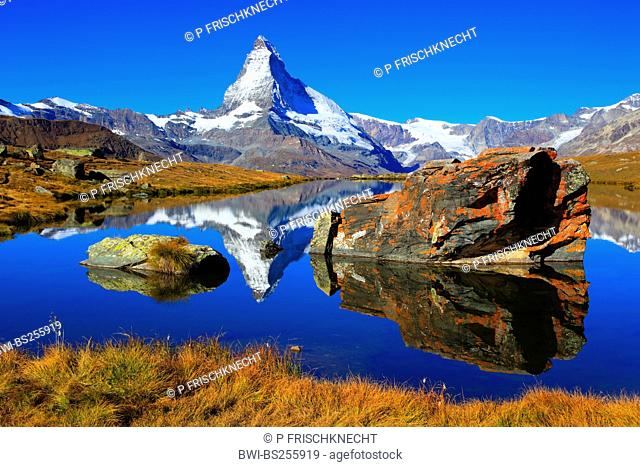 view from a mountain lake at the Matterhorn under clear blue sky, Switzerland, Valais