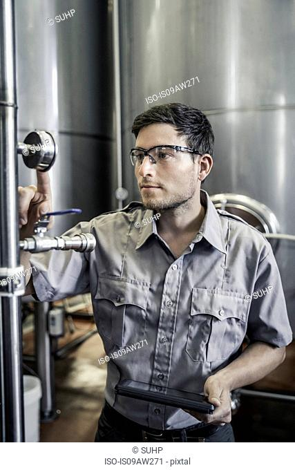 Young man in brewery holding digital tablet checking gauge
