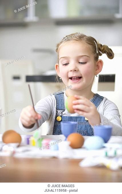 Young girl painting eggs in kitchen