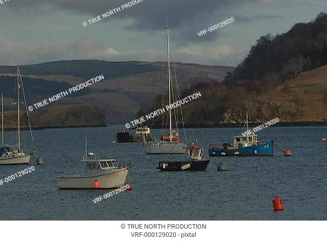 GV, Mwide shot of fishing boats on calm sea, land in background, industry, picture postcard. Mull, Scotland, UK