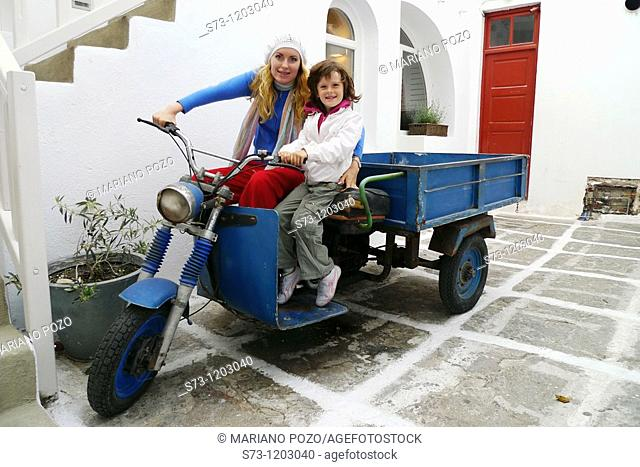 Young woman and 7 years old girl in a motorcycle in Mykonos, Cyclades Islands, Greece