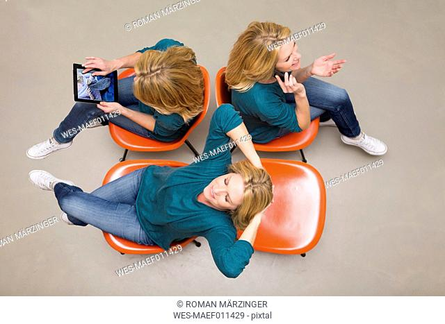 Woman sitting on chairs using portable devices, multitasking