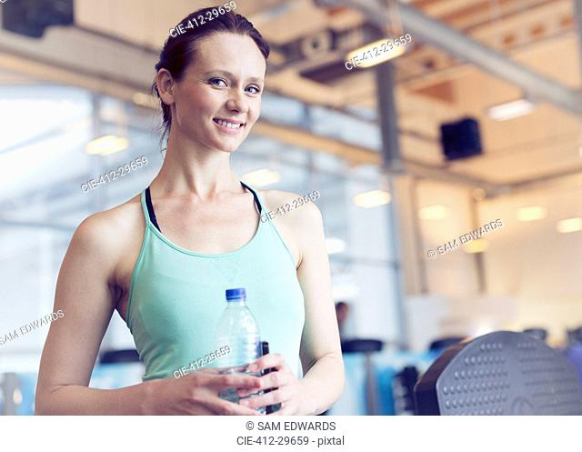 Portrait smiling woman drinking water at gym