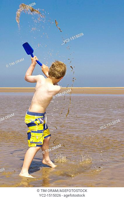 A seven year old boy playing on the beach at Wells-next-the-sea , Norfolk , England , Britain , Uk