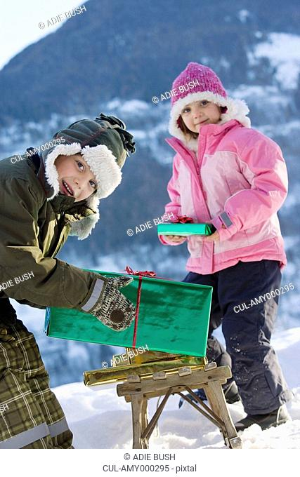 Boy and girl with presents in the snow