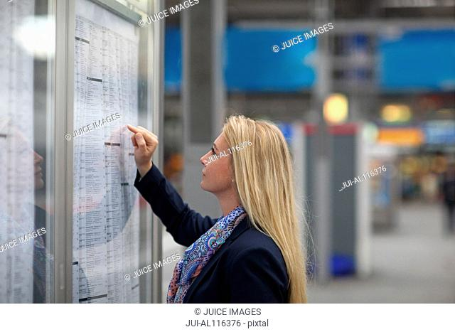 Mid adult woman studying train timetable, Munich, Bavaria, Germany, Europe