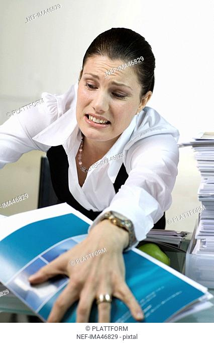 A woman in an office with a large pile of paper