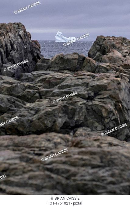 View of iceberg in sea through rocks on shore, Fogo Island, Newfoundland, Canada