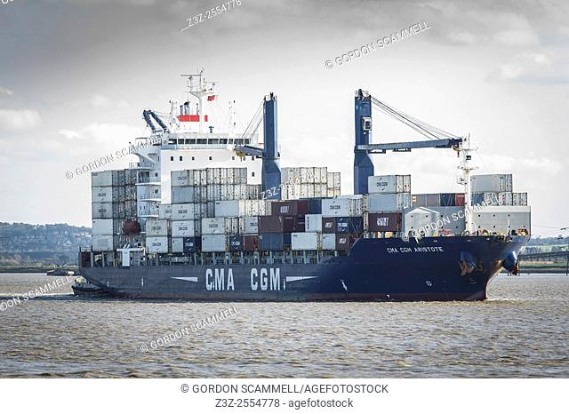 The fully laden container ship CMA CGM Aristote steams upriver on the River Thames