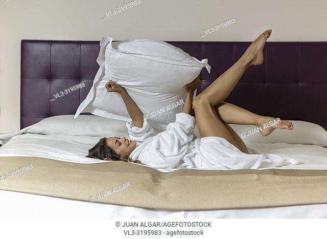 Side view of smiling young woman with pillow in hands reveling in morning in hotel bed