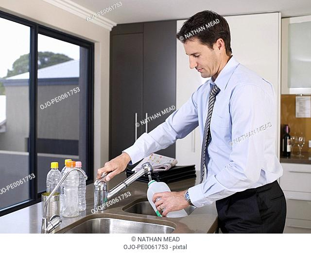 Businessman in kitchen rinsing out plastic bottle
