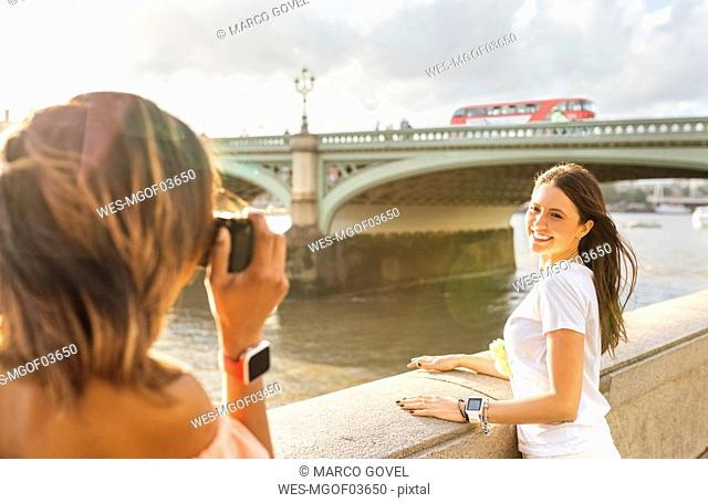 UK, London, woman taking a picture of her friend near Westminster Bridge