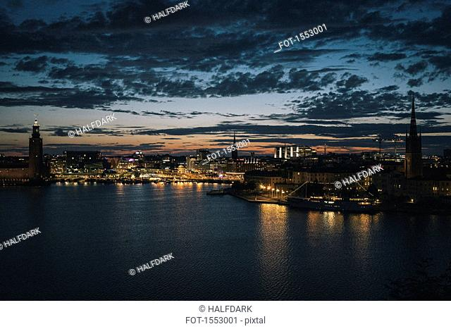 Scenic view of waterfront and illuminated city against sky at dusk, Stockholm, Sweden