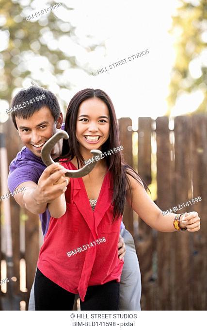 Man helping girlfriend throw horseshoe outdoors