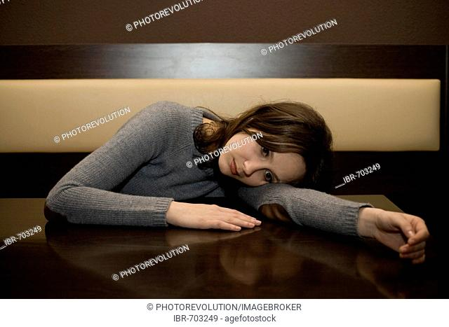 Young woman leaned over a table at a bar, looking depressed