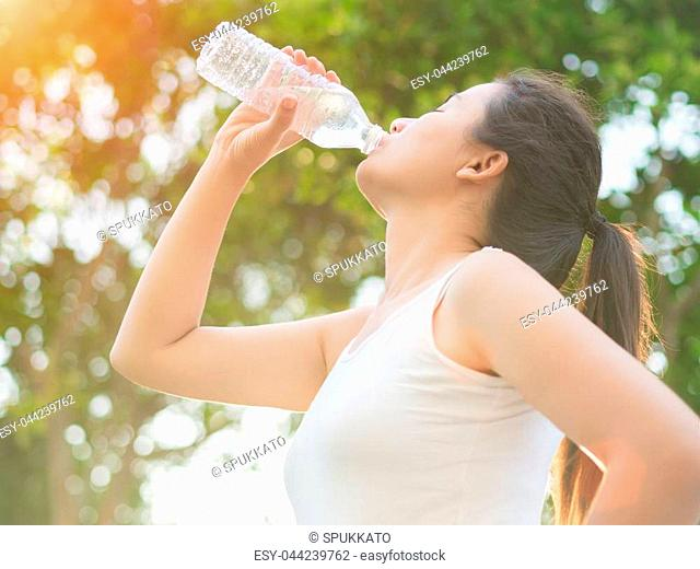 Happy beautiful young woman drinking water from bottle with tree leave background. Health care concept