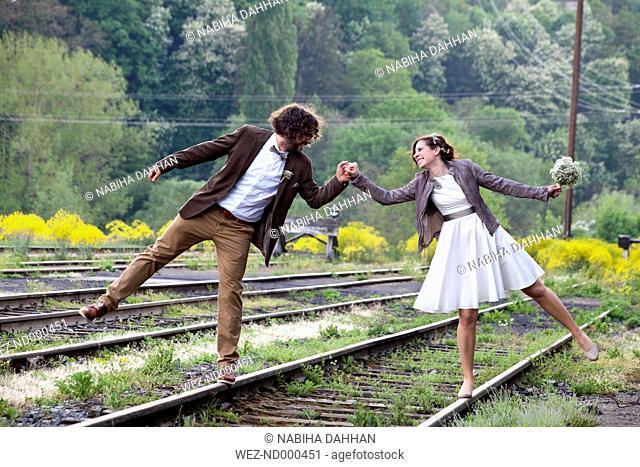 Bridal couple balancing on rails