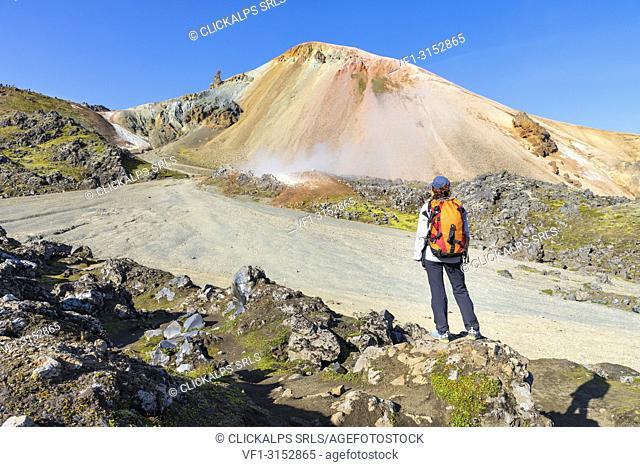 Graenagil footpath: a trekker is looking the Brennisteinsalda mountain from the Laugahraun lava field in Landmannalaugar (Fjallabak Nature Reserve, Highlands