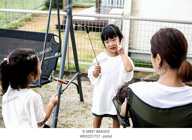 Two Japanese girls holding sausages on skewers and woman in a backyard