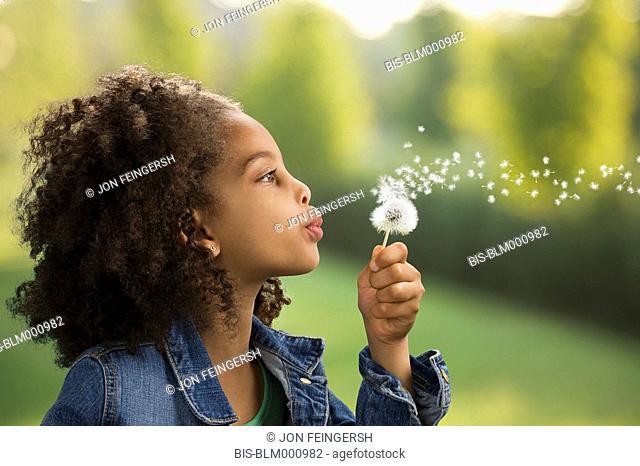 African girl blowing dandelion seeds