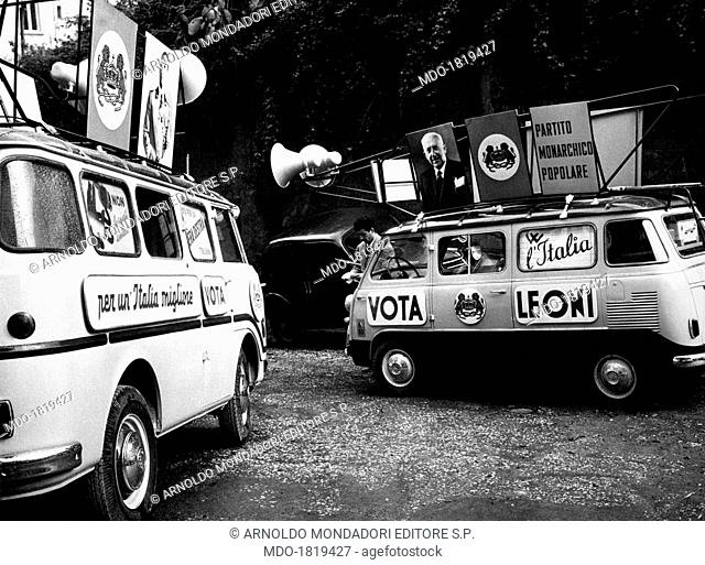 Two mini-vans with speakers and Italian politician and founder of the People's Monarchist Party (PMP) Achille Lauro's image standing on a dirty road