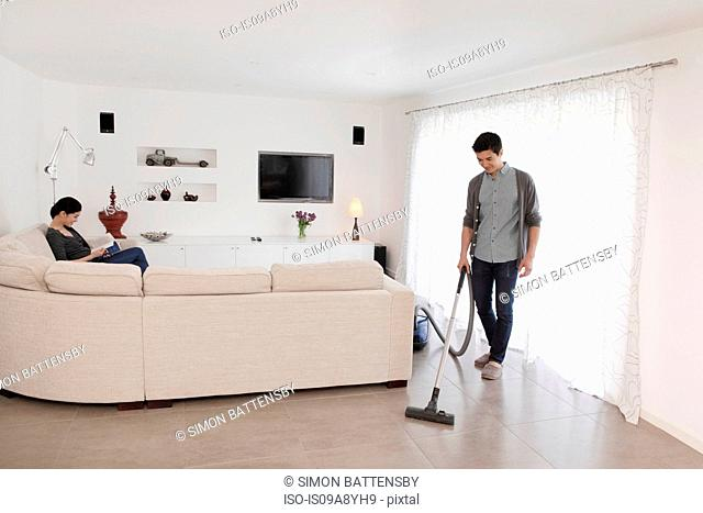 Man vacuuming living room floor