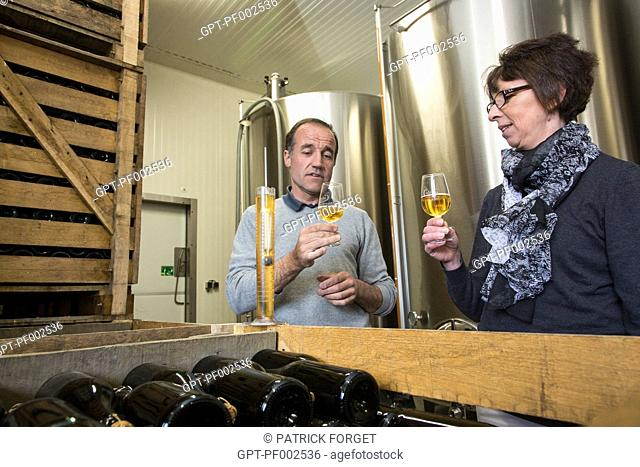 NATHALIE DE WEVER, SHOP OWNER AND MEMBER OF THE LOCAVORE MOVEMENT, TASTING CIDER MADE BY ERIC DORE, CIDER-MAKER, IN THE CELLARS OF THE PRESSOIR D'OR, BOISEMONT