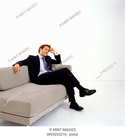 Businessman wearing dark suit sitting indoors on a sofa, hand on head, smiling