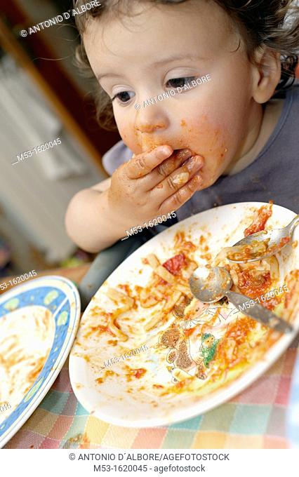 A seventeen months old baby girl eat tomato sauce paste with her hands  Selective focus on the mouth