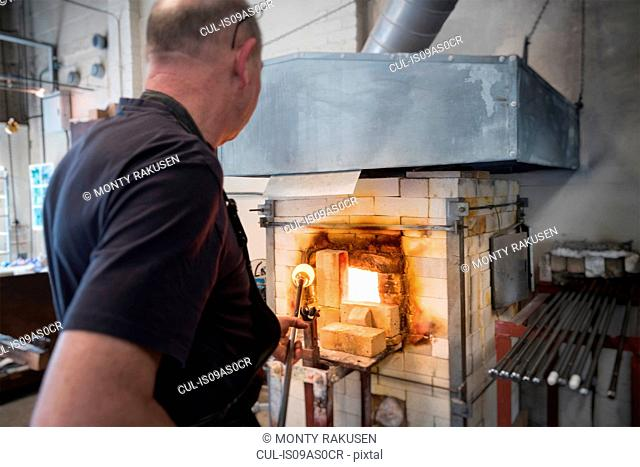 Glassblower drawing molten glass from furnace