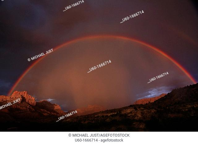 A full rainbow stretches across the sky during a lightning and thunderstorm at Zion National Park, Utah