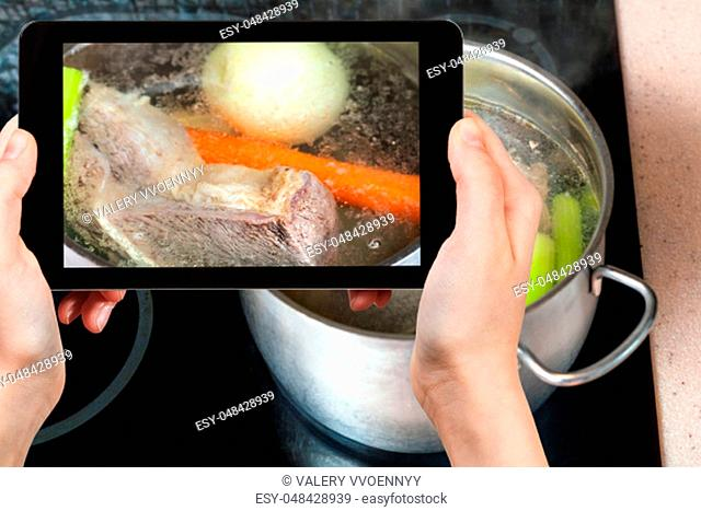 travel concept - visitor photographs of cooking soup with boiling beef broth in steel stewpan close up on caramic stove on smartphone
