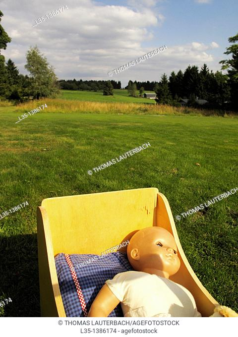 Old doll in a pram, Harz highlands in the background, Lower Saxony, Germany