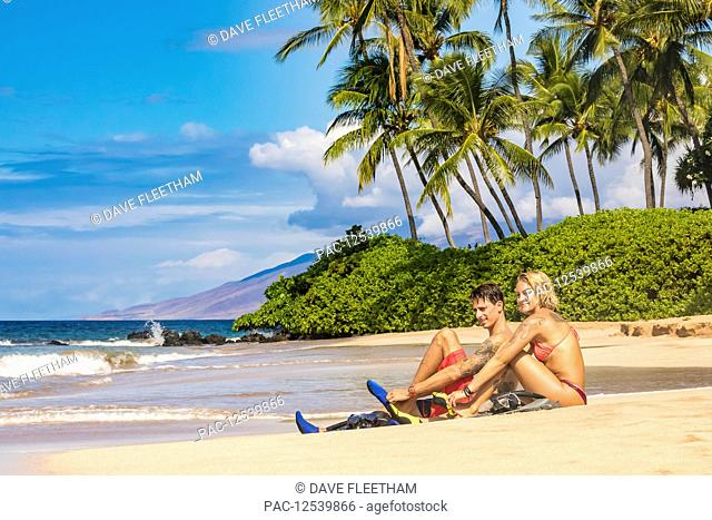 A couple with snorkel gear on a beach with palm trees; Maui, Hawaii, United States of America